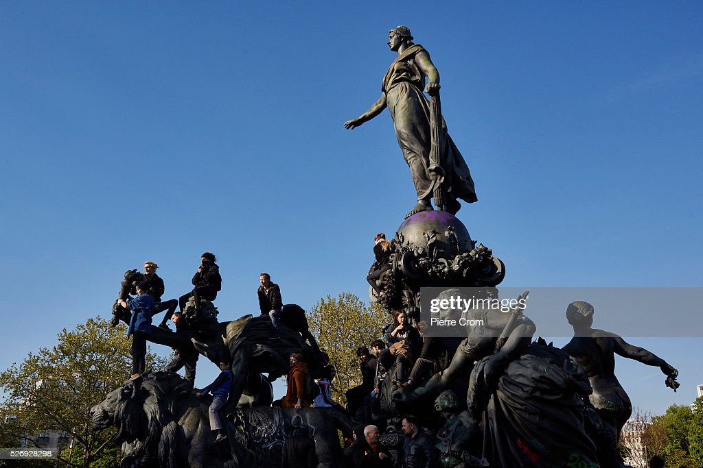 Protesters sit atop a monument on Place de la Nation during the May Day rally on May 01, 2016 in Paris, France. Violence broke out as people took to the streets to demonstrate against proposed labour law reforms.