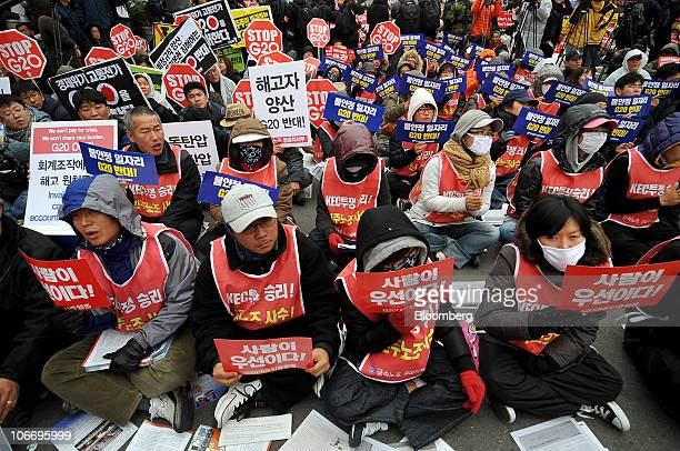 Protesters sit down during a demonstration against the G20 summit in Seoul South Korea on Thursday Nov 11 2010 As many as 10000 laborers and...