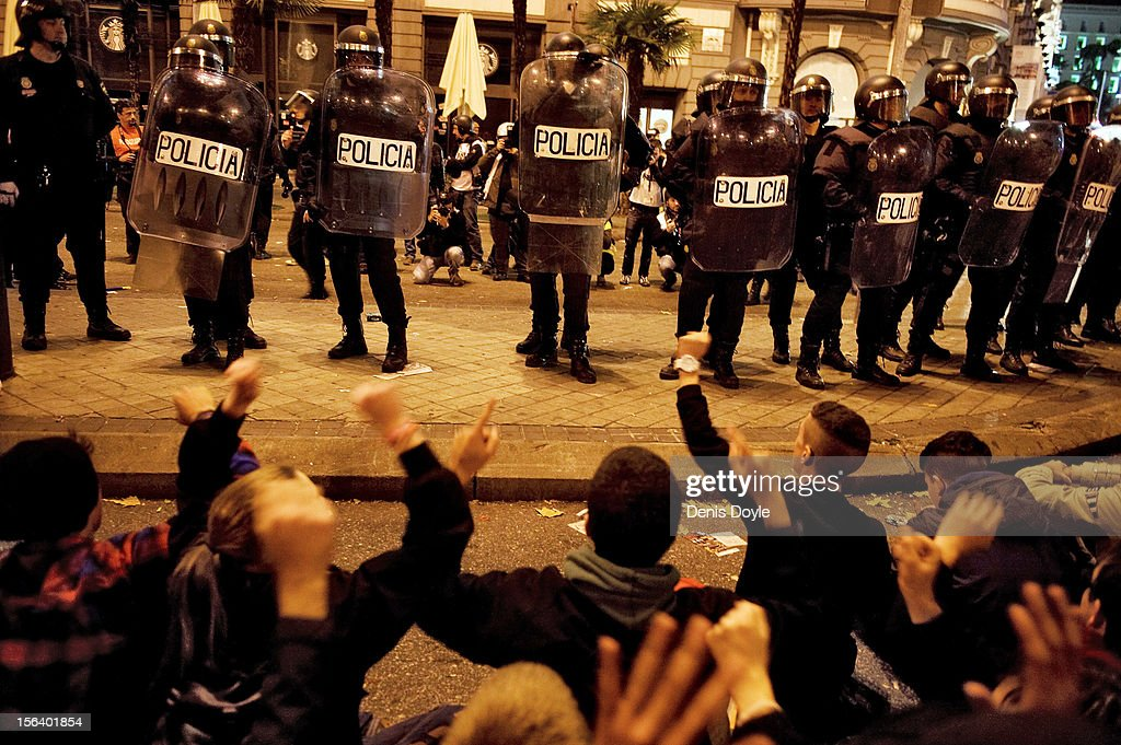 Protesters sit down in front of a line of police during a demonstration near the Spanish parliament on November 14, 2012 in Madrid, Spain. A coordinated general strike by unions in Spain and Portugal has paralyzed public transport in the two countries with further strikes planned across Europe. The strike against the governments' austerity measures have force hundreds of flights to be cancelled and factories and ports to come to a standstill.