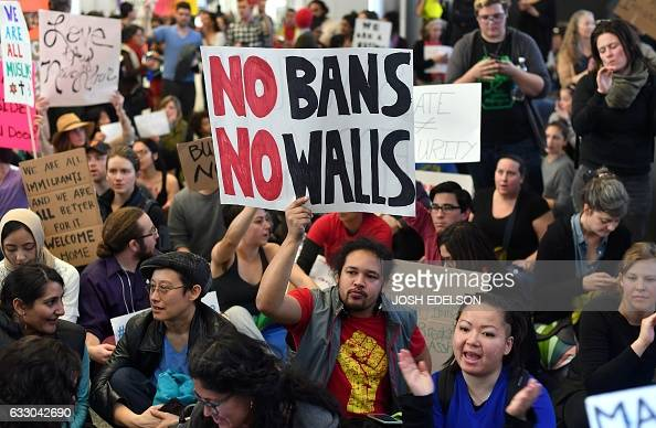 TOPSHOT Protesters sit in the international terminal at San Francisco International Airport in San Francisco California on January 29 2017 US...