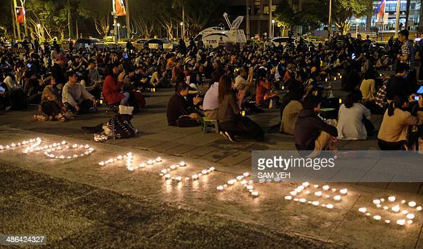 Protesters sit on the ground next to candles during an antinuclear demonstration in Taipei on April 24 2014 Former Taiwanese opposition leader and...