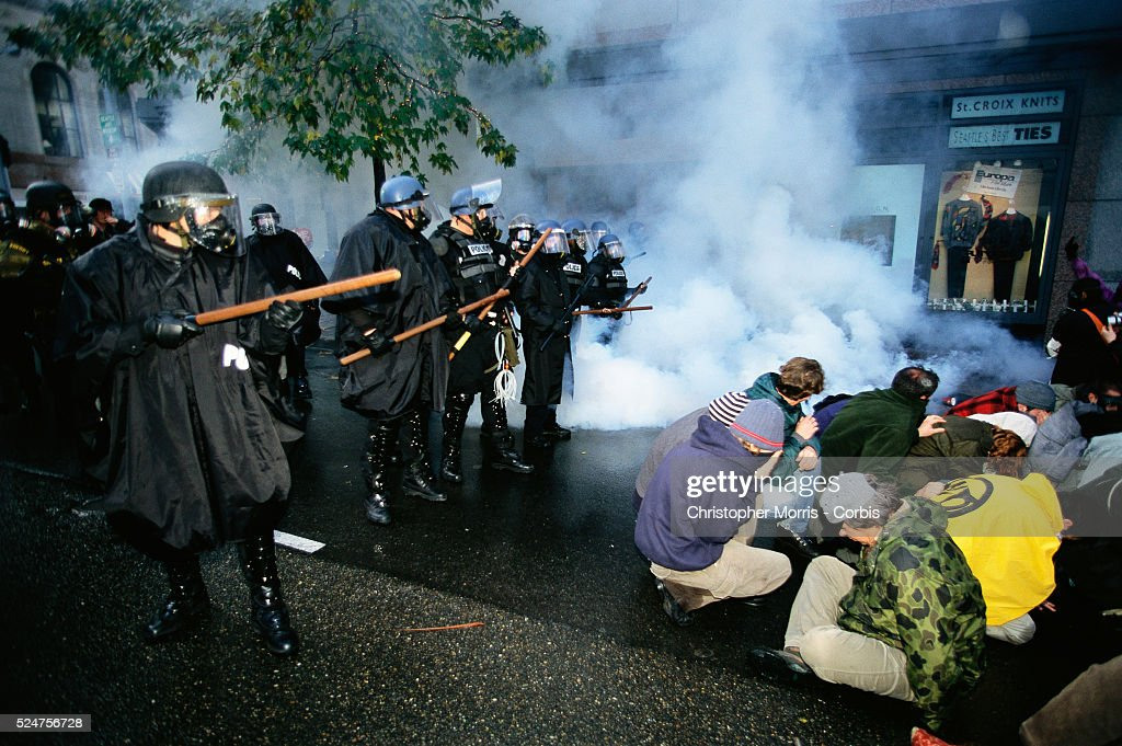 Protesters sitting on the ground are confronted by riot police during the World Trade Organization's 1999 conference in Seattle What started out as a...