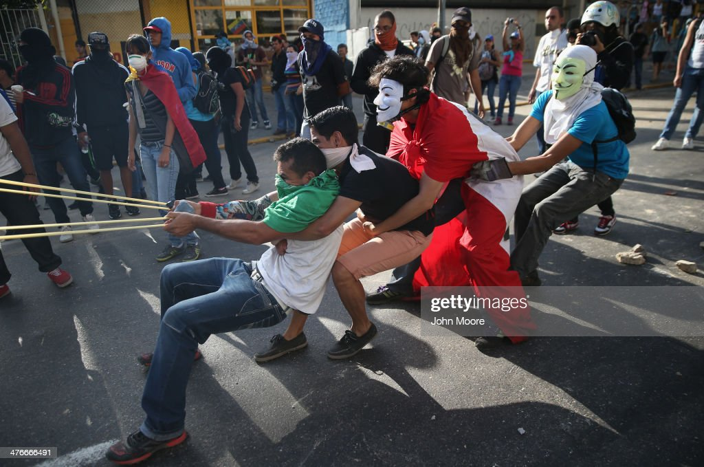 Protesters sling stones at Venezuelan national guard troops during an anti-government demonstration on March 4, 2014 in Caracas, Venezuela. Wednesday marks the first anniversary of Hugo Chavez' death on March 5, 2013. For three weeks protesters have blocked roads throughout the country and clashed with security forces of the government of Chavez' chosen successor President Nicolas Maduro.