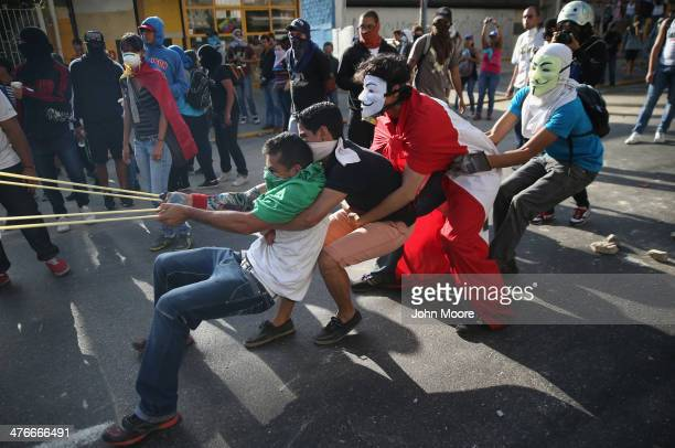 Protesters sling stones at Venezuelan national guard troops during an antigovernment demonstration on March 4 2014 in Caracas Venezuela Wednesday...