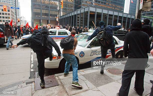 Protesters smash police vehicles in the Toronto's downtown core June 26 2010 after a small group of anarchists broke from the main anti G20...
