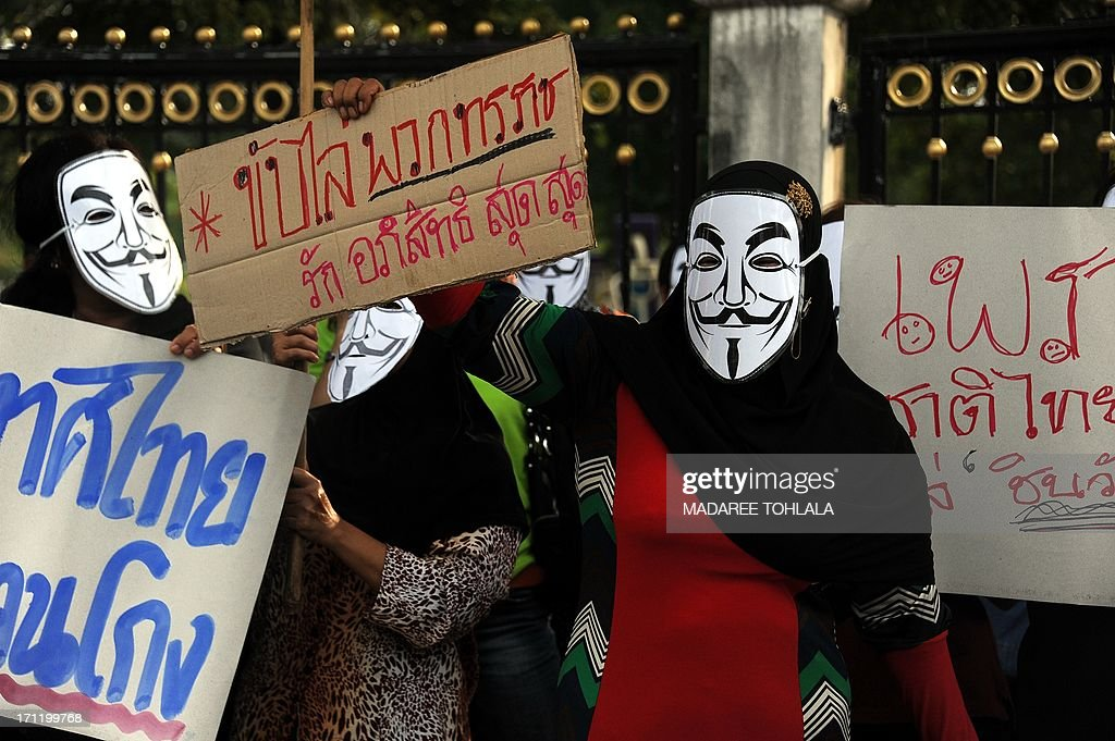 Protesters, some wearing Guy Fawkes masks, gather in Thailand's restive southern province of Narathiwat on June 23, 2013. Hundreds of people gathered to protest against the former prime minister Thaksin Shinawatra and the current government led by his sister Thai Prime minister Yingluck Shinawatra.