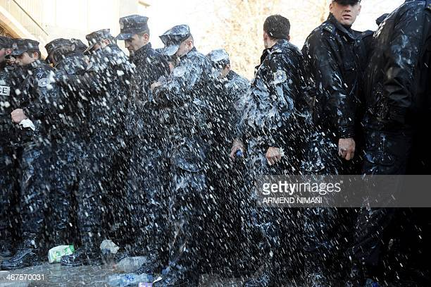 Protesters splash police officers with milk as demonstrators gather in Pristina on February 7 2014 to demand the resignation of the dean of the...