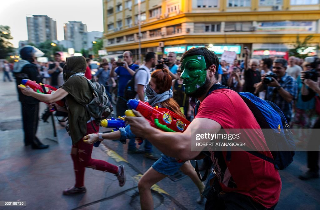 Protesters spray paint with toy water guns on the facade of the Ministry of Justice building during an anti-government protest in Skopje on May 31, 2016, in a series of protests dubbed Colourful Revolution. Macedonia's president revoked on May 27 the pardons he had granted to 22 politicians implicated in a wiretapping scandal, after the move sparked outrage inside and outside the troubled Balkan country. / AFP / Robert ATANASOVSKI