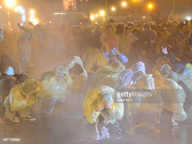 Protesters squat on the ground as water is sprayed at them outside Taipei Railway Station during an antinuclear demonstration in Taipei on April 28...