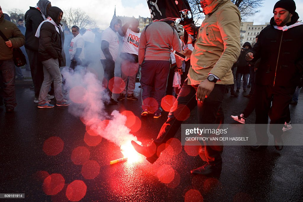Protesters stand around a burning flare on the Place de la Nation in Paris on February 9, 2016, during a demonstration by non-licensed private hire cab drivers, known in France as VTC (voitures de tourisme avec chauffeur or tourism vehicles with chauffeur). VTC drivers continued a fifth day of protests on February 9 against measures granted by the French prime minister to taxi drivers. / AFP / Geoffroy Van der Hasselt