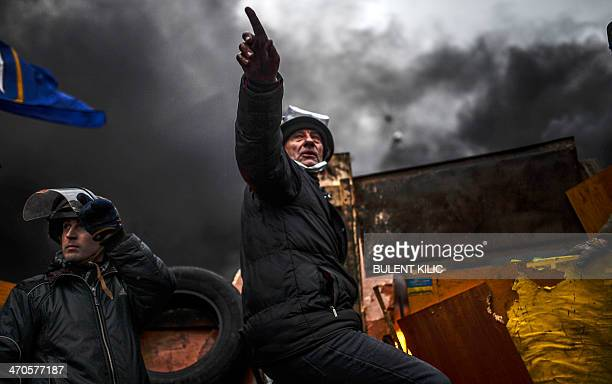 Protesters stand behind barricades during clashes with police on February 20 2014 in Kiev Ukraine's embattled leader announced a 'truce' with the...