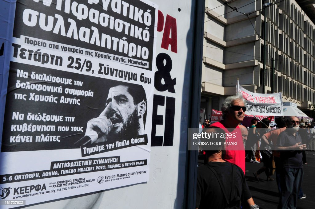 Protesters stand by a poster calling for a anti-fascism demonstration on September 24, 2013. The fatal stabbing of 34-year-old hip hop artist Pavlos Fyssas on September 18 touched off street protests and prompted authorities to take a harder stance against Golden Dawn. Two top Greek police chiefs quit in a shake-up on Monday after the murder of an anti-fascist musician by an alleged member of neo-Nazi party Golden Dawn sparked protests, and led to a probe of a possible police connection.