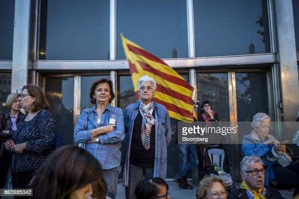 Protesters stand in front a Catalan flag during a vigil to demand the release of imprisoned seperatist leaders Jordi Sanchez head of the Catalan...