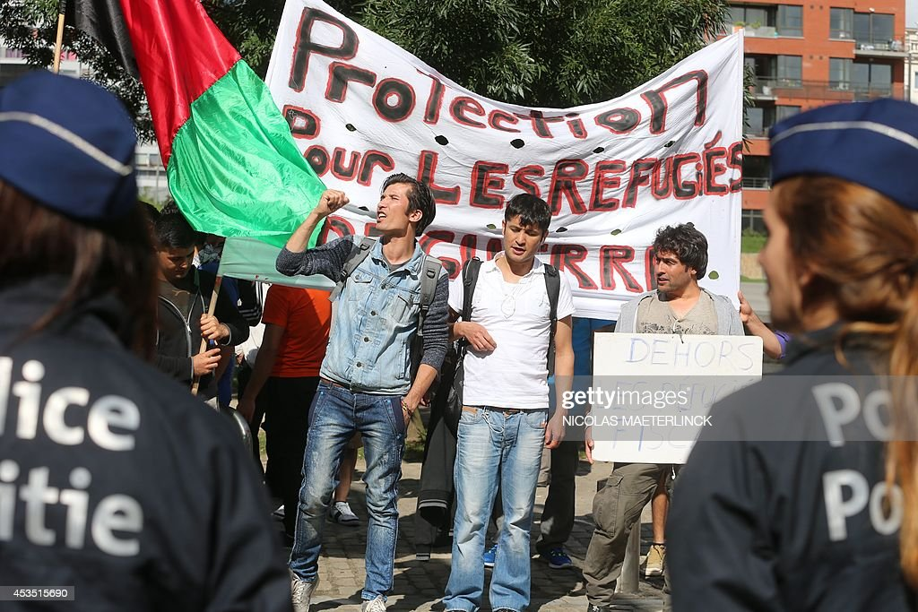 Protesters stand in front of a banner reading 'Protection for war refugees' during a demonstration in favour of Afghan refugees' rights, on August 12, 2014, in Brussels.