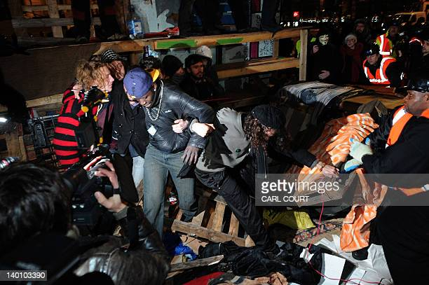 Protesters stand in front of a makeshift barricade at the Occupy protest camp outside Saint Paul's Cathedral in central London early on February 28...