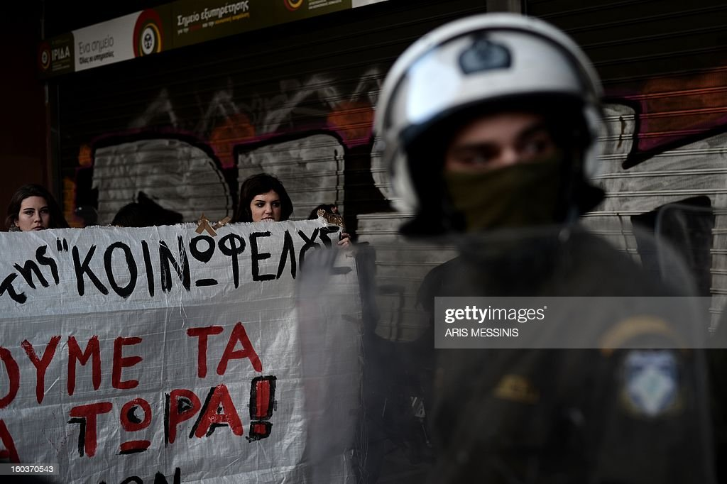 Protesters stand in front of riot police stand outside the Labour Ministry in Athens on January 30, 2013. Police were called in on Wednesday to dislodge around 30 Communist unionists from the labour ministry in a protest against new pension cut plans. The unionists were arrested and police used tear gas outside the building to disperse a larger group of protesters demanding their release. AFP PHOTO / ARIS MESSINIS