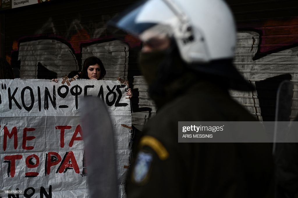 Protesters stand in front of riot police stand outside the Labour Ministry in Athens on January 30, 2013. Police were called in on Wednesday to dislodge around 30 Communist unionists from the labour ministry in a protest against new pension cut plans. The unionists were arrested and police used tear gas outside the building to disperse a larger group of protesters demanding their release.