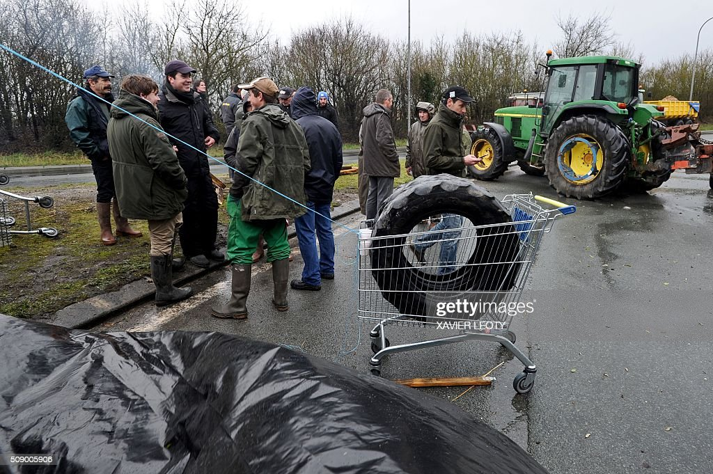 Protesters stand near a tractor as they block a road near Saintes, western France, on February 8, 2016, during a demonstration by farmers against the purchase price of their products by supermarkets. Over 100 tractors were used by mostly pig and dairy farmers to block strategic points giving access to the city, disrupting traffic and closing an interchange of the A10 motorway. / AFP / XAVIER LEOTY