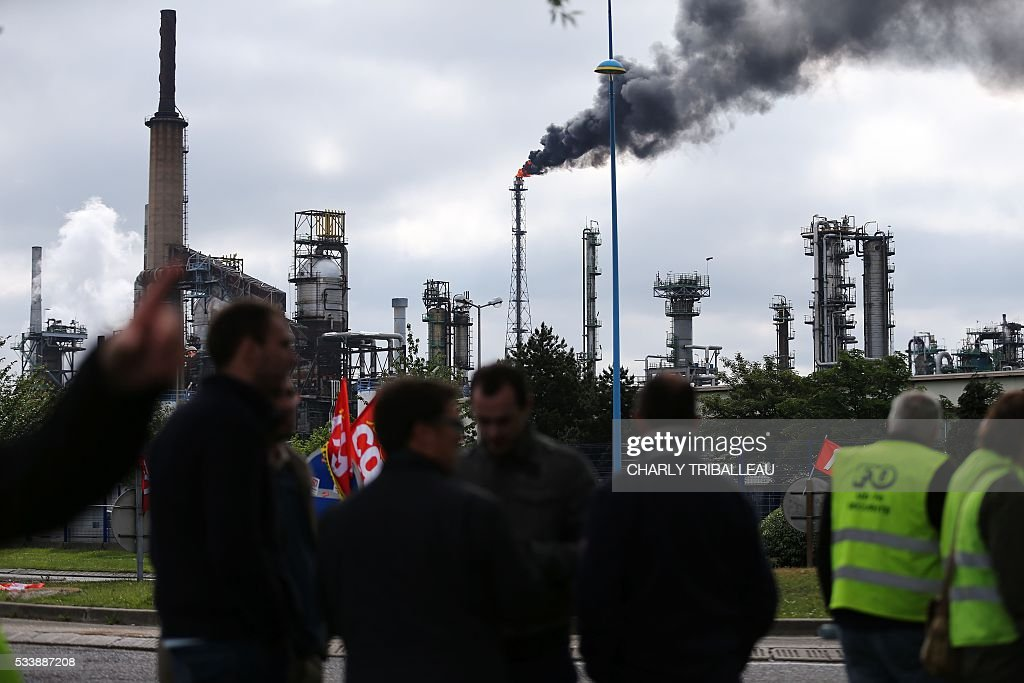 Protesters stand near the ExxonMobil oil refinery in Notre-Dame-de-Gravenchon, northwestern France, on May 24, 2016, following blockades of several oil refineries and fuel depots in France by protesters opposed to government labour reforms. A strike called by the Force Ouvriere (FO) and General Confederation of Labour (CGT) French workers' unions started slowing on May 24 at the ExxonMobil oil refinery in Notre-Dame-de-Gravenchon, without disrupting operations at France's second largest refinery. / AFP / CHARLY