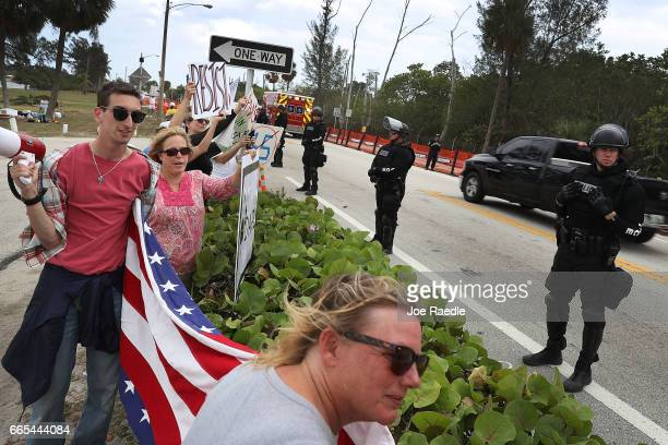 Protesters stand near the road as a convoy bearing Chinese President Xi Jinping was to drive past on his way to visit US President Donald Trump at...