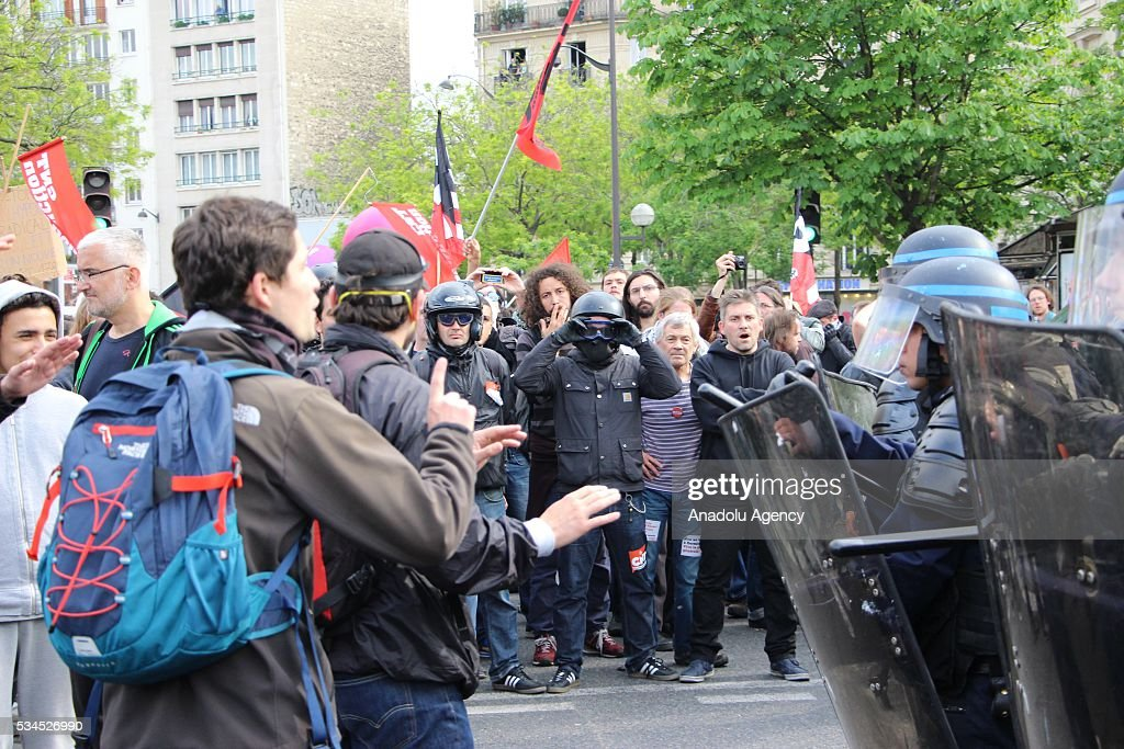 Protesters stand next to French police during the protests against French government's labor law reform in Paris, France on May 26, 2016.
