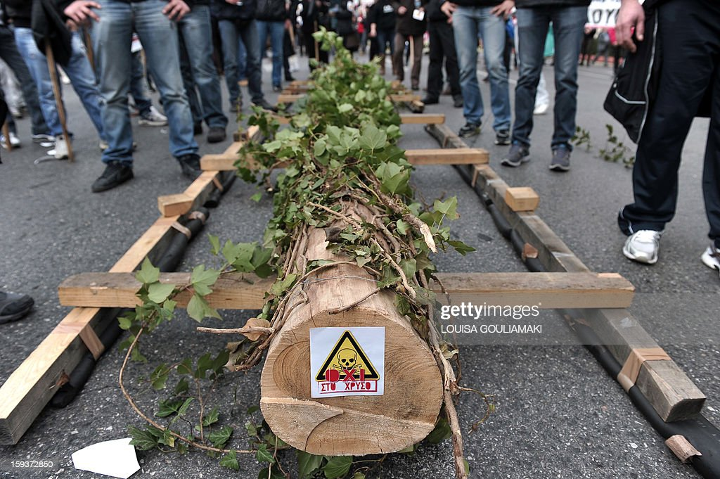 Protesters stand on January 12, 2013 next to a tree trunk, bearing a sticker reading 'No to gold,' in the center of Athens during a demonstration against a Canadian gold mining investment in the northern region of Halkidiki that is feared to be causing irreversible damage to the local environment. A number of citizens' groups, backed by the radical leftist party Syriza that is now the second largest group in parliament, have been trying to scupper the project since 2011, when the government allowed Hellenic Gold -- a subsidiary of Canadian firm Eldorado Gold -- to dig in the area. AFP PHOTO/ LOUISA GOULIAMAKI