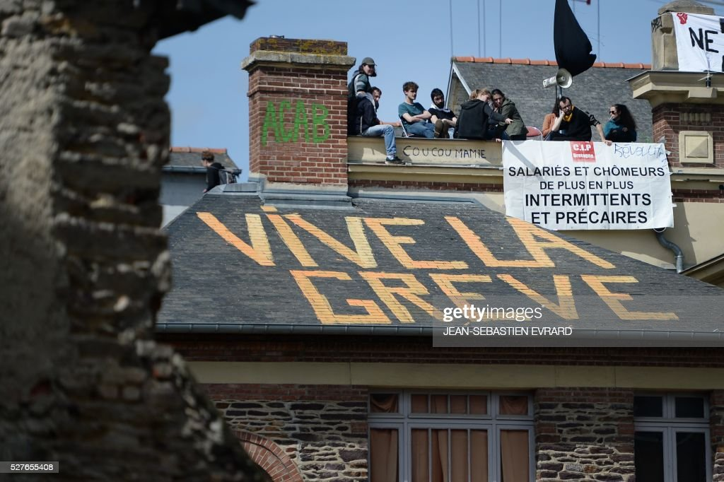 Protesters stand on the roof of the People's house on which is written 'long live to the strike' on May 3, 2016 in Rennes, western France, during a protest against the government's planned labour law reforms. High school pupils and workers protest against deeply unpopular labour reforms that have divided the Socialist government and raised hackles in a country accustomed to iron-clad job security. / AFP / JEAN