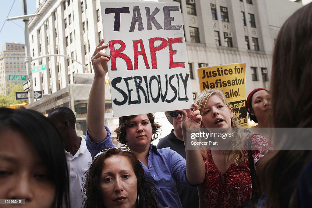 Protesters stand outside of a Manhattan court as former IMF director Dominique StraussKahn exits the court on August 23 2011 in New York City The...
