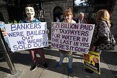 Protesters stand outside the government buildings as Irish Finance Minister Michael Noonan announces the 2015 Irish budget in Dublin on October 14...