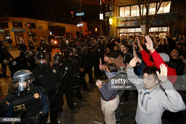 Protesters stand raise their hands in front of a police line during a demonstration over recent grand jury decisions in policeinvolved deaths on...