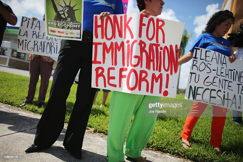 Protesters stand together as they hold a protest to ask their congress people to make immigration reform a reality on August 16, 2013 in Miami, Florida. The protesters were targeting Representatives Ileana Ros-Lehtinen and Mario Diaz-Balart to do more to win Comprehensive Immigration Reform with a path to citizenship.