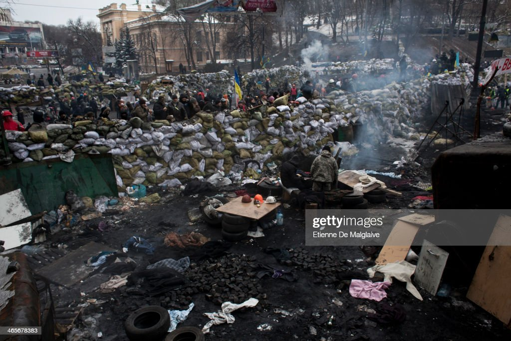 Protesters stand watch behind a barricade on January 28, 2014 in Kiev, Ukraine. While Ukrainian parliament holds an emergency session, standoff continues on Hrushevskoho street between anti-government protesters and riot police.