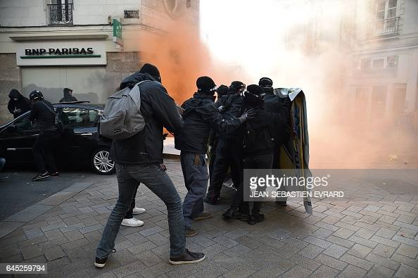 TOPSHOT Protesters take cover behind a makeshift shield during clashes with riot police on the edge of a demonstration against the visit of French...