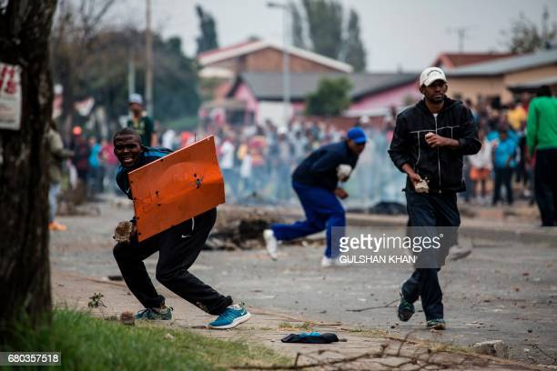 Protesters take cover during clashes with South African riot police in the Eldorado Park district in Johannesburg on May 8 2017 following a...