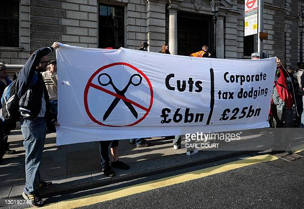 Protesters take part in a demonstration against corporate tax avoidance outside the Her Majesty's Revenue and Customs offices in central London on...