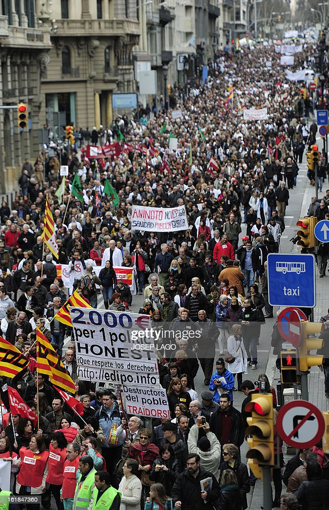 Protesters take part in a demonstration against plans to cut medical spending and privatise hospital services in Barcelona on February 17, 2013. Thousands of Spanish doctors, nurses and other health care workers, many wearing white lab coats, demonstrated today in 16 cities against budget cuts and plans to partly privatise medical services. Nationally, Prime Minister Mariano Rajoy's government has slashed health spending by seven billion euros (9.1 billion USD) a year as part of a campaign to squeeze 102 billion euros out of the crisis-racked country's budget by 2014.