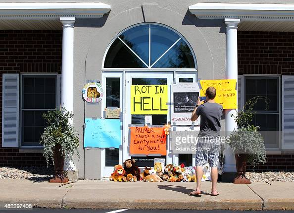 Protesters take photos of signs condemning the alleged poaching of Cecil the lion in the parking lot of hunter Dr Walter Palmer's River Bluff Dental...