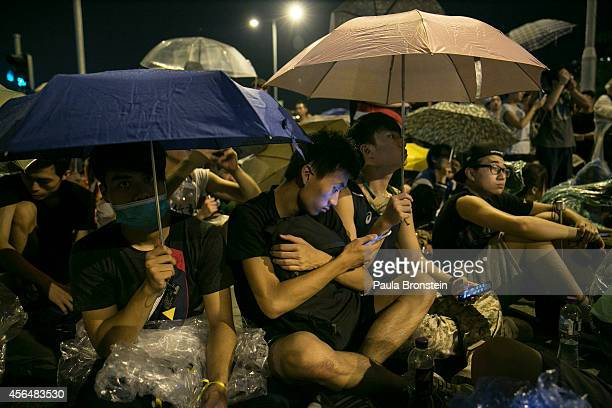 Protesters take shelter from the rain as they sit overnight outside the legislative government complex on October 2 2014 in Hong Kong Hong Kong...