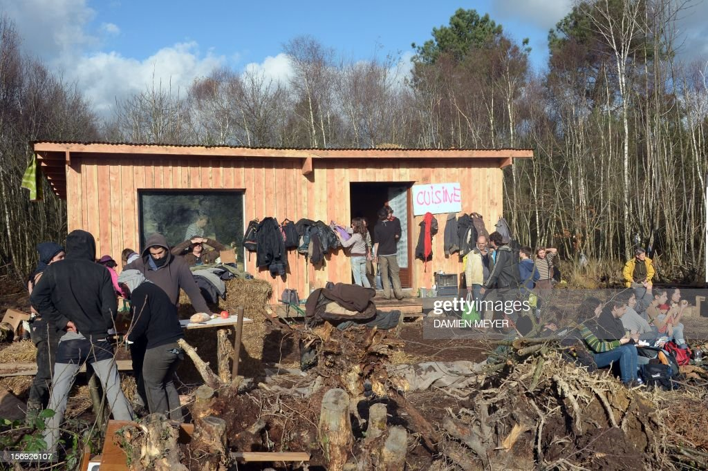 Protesters take their lunch after re-occupying a protected swampland on November 25, 2012 in Notre-Dame-des-Landes, near Nantes in western France, one day after squatters' eviction and clashes with anti-riot policemen. The airport, which is scheduled to replace the current airport at Nantes in 2017, is a pet project of Socialist Prime Minister Jean-Marc Ayrault, who was the city's mayor from 1989 until this year.
