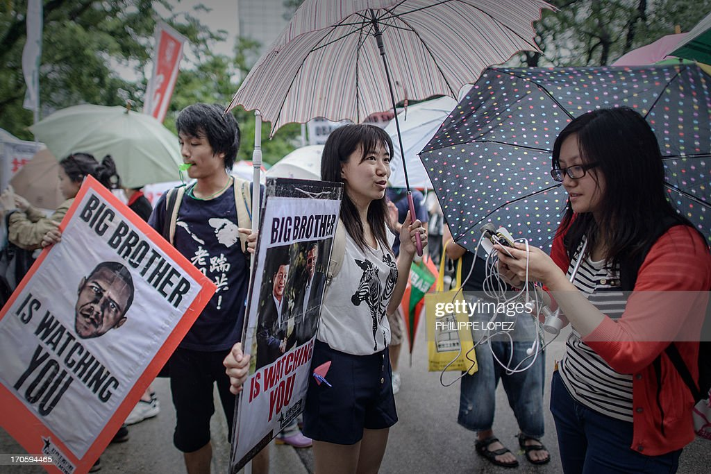 Protesters talk to the press as they march to the US consulate during a protest in support of Edward Snowden from the US in Hong Kong on June 15, 2013. Snowden, a former CIA technical assistant, is in hiding in Hong Kong after he arrived in the city on May 20 and blew the lid on a vast electronic surveillance operation by the National Security Agency, which has hit targets in China and Hong Kong. AFP PHOTO / Philippe Lopez