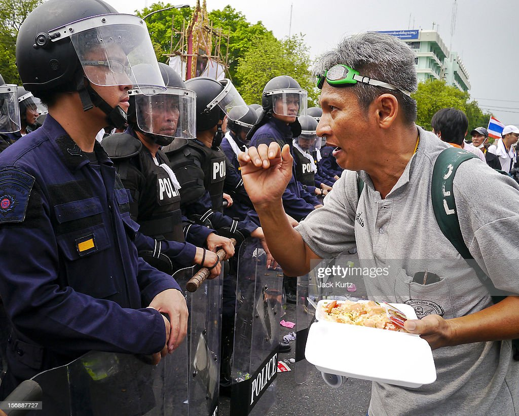Protesters taunt Thai riot police during a large anti government protest on November 24, 2012 in Bangkok, Thailand. The Siam Pitak group, which sponsored the protest, cited alleged government corruption and anti-monarchist elements within the ruling party as grounds for the protest. Police used tear gas and baton charges againt protesters.