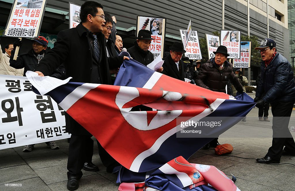 Protesters tear a North Korean national flag during a demonstration against North Korea's nuclear test in Seoul, South Korea, on Tuesday, Feb. 12, 2013. North Korea conducted its third underground nuclear test today, underscoring a disregard for an international community that has already isolated the totalitarian state from the global economy. Photographer: SeongJoon Cho/Bloomberg via Getty Images