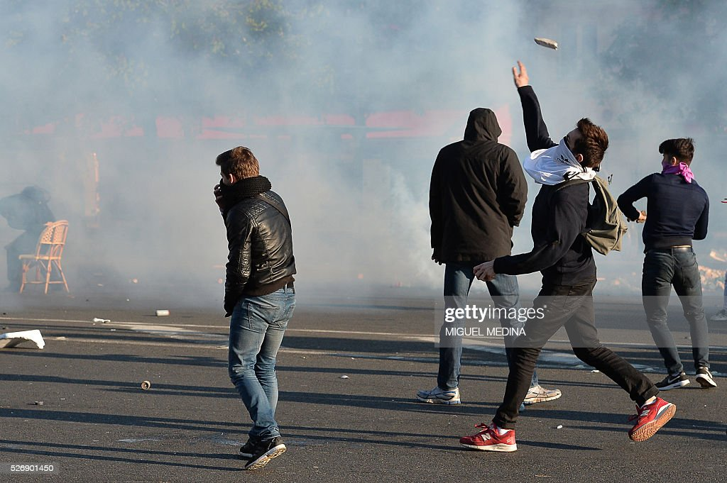 Protesters thow projectiles as they clash with police on the Place de la Republique at a traditional May Day demonstration on May 1, 2016, in Paris.