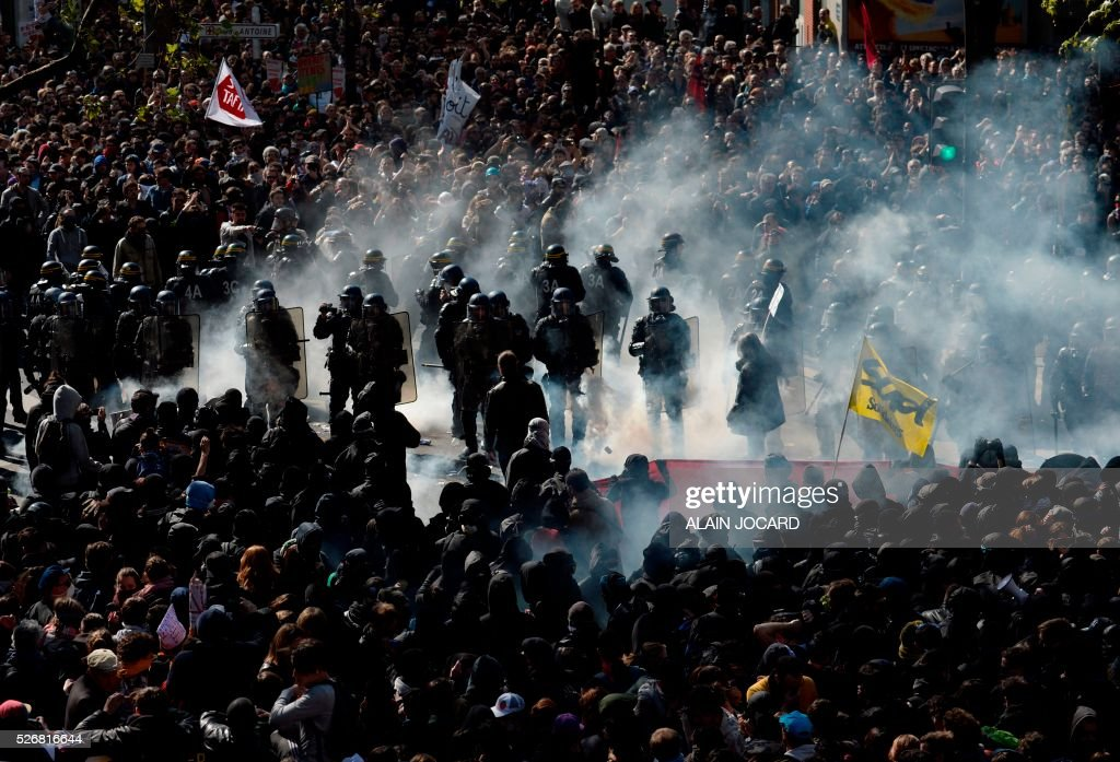 Protesters throw a smoke grenades towards French anti riot police during a clash during the traditional May Day demonstration in Paris on May 1, 2016.