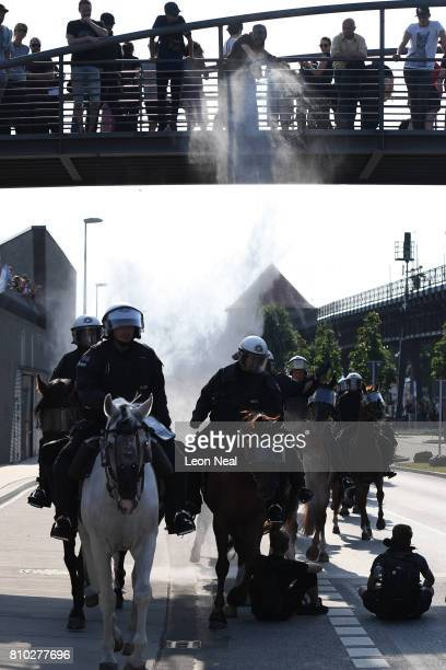 Protesters throw a white powdered substance on the police as they pass underneath as an antiG20 march continues on July 7 2017 in Hamburg Germany...