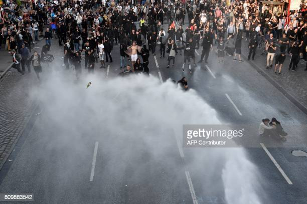 Protesters throw beer bottles as police use water cannon during the 'Welcome to Hell' rally against the G20 summit in Hamburg northern Germany on...