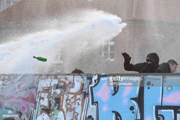TOPSHOT Protesters throw beer bottles as they shield themselves from water cannon spray during the 'Welcome to Hell' rally against the G20 summit in...