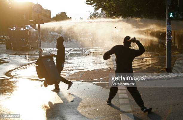 Protesters throw bottles at riot police using water cannon on July 7 2017 in Hamburg northern Germany where leaders of the world's top economies...