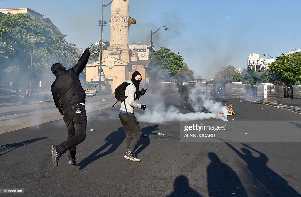 Protesters throw projectiles towards French anti riot police blocking the street during the traditional May Day demonstration in Paris on May 1, 2016.