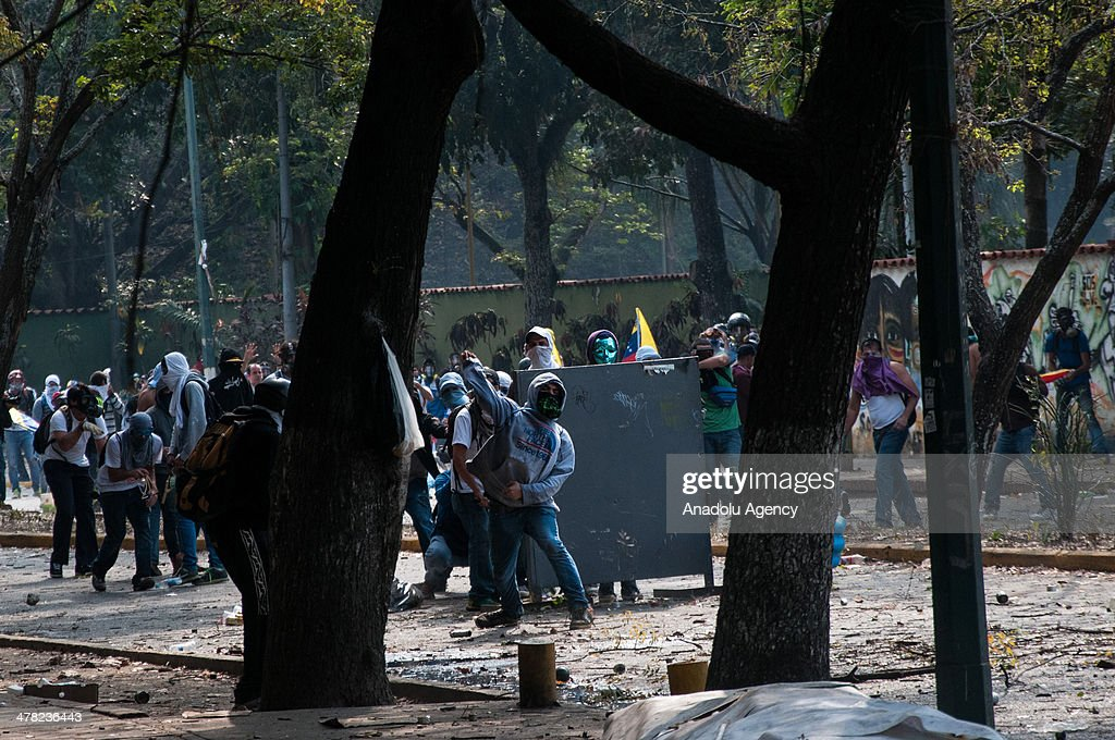 Protesters throw stones at National Bolivarian Guard members during the anti-government protests in Caracas, Venezuela on March 12, 2014. Three people including a university student and a National Guard member, were shot death and several others injured on Wednesday during the anti-government protests in Venezuela.